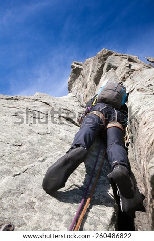 View from below of a climber while climbing a steep rock wall. Western Alps, Italy, Europe. - stock photo