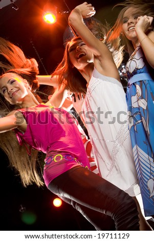 View from below of glamorous girls dancing at discotheque - stock photo