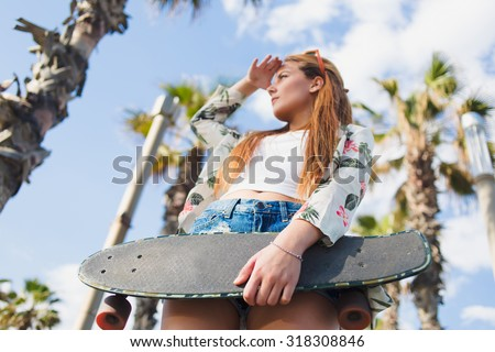 View from below of trendy woman holding skateboard with copy space for your brand while standing against tropical sky in sunny day, hipster girl with long board holding hand near forehead looking away - stock photo
