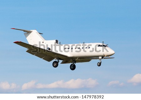 view from below on the white private jet with the gear against the blue sky - stock photo