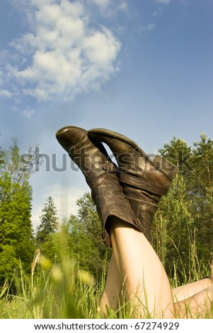 view from bottom on legs of resting women on meadow - stock photo