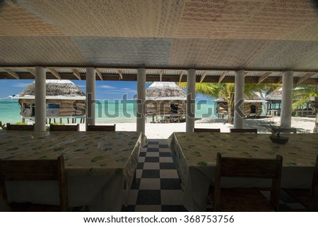 View from dining room next to the beach with palm bungalows and azure blue sea in polynesia - stock photo