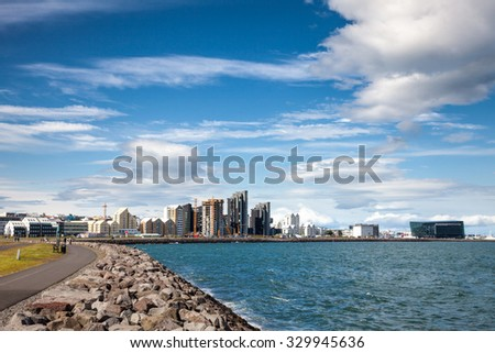 View from embankment to  Midborg district in Reykjavik, Iceland, with waterfront buildings and Harpa concert hall  - stock photo