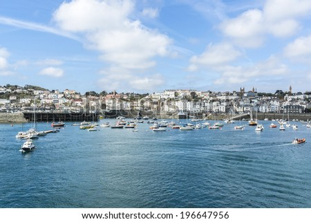 View from English Channel to town of Saint Peter Port, Guernsey, UK. Saint Peter Port - capital of Guernsey as well as main port. - stock photo