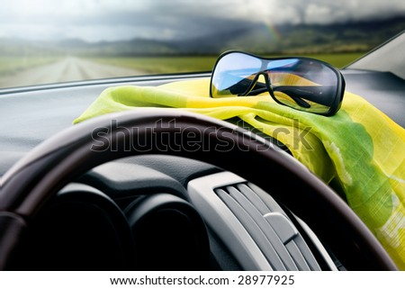 View from inside the car on a country road with the sunglasses in the foreground