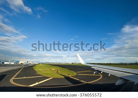 View from inside window seat, airplane taking off from runway with blue sky background - stock photo