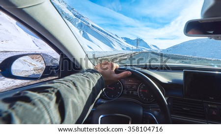 view from luxury car inside with part of interior and mirror with driver male hand on  the steering wheel on danger straight ice asphalt road during sunny day with snowy mountains in background  - stock photo