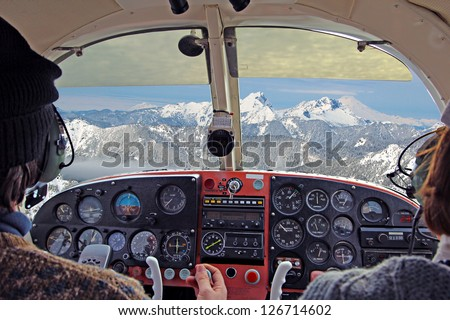 view from over snow covered peaks while flying in small plane - stock photo