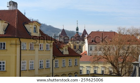 View from point on Charles Bridge near statue of St. Vincent Ferrer toward Church of Our Lady under the chain and Petrin Hill, Prague, Czech Republic. - stock photo