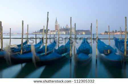 View from Saint Mark Square (Piazza San Marco). Motion blurred gondolas due to long exposure - stock photo