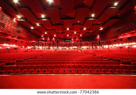 View from stage on ceiling and rows of comfortable red chairs in illuminate red room cinema - stock photo