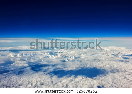 View from the airplane of a cumulus white clouds and amazing blue sky background with copy space for your text message or promotional content, advertising field - stock photo
