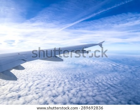 view from the airplane window, above the clouds - stock photo