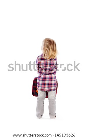 View from the back of a small blond girl in jeans and a plaid shirt with a suitcase held in front of her waiting to leave on a summer vacation - stock photo