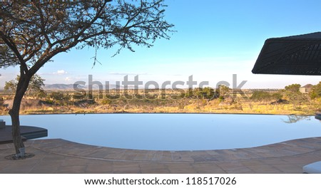 View from the back pool deck of the Bilia Lodge with infinity pool and watering hole below. Serengeti National Park, Tanzania - stock photo