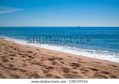 View from the beach on the blue sea with small island or rock on the horizon