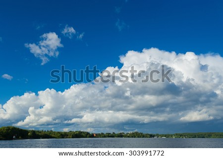 View from the board of a sailing yacht on the waters, sailing ships and the forest growing along the coast, as well as people's homes. A huge white cloud over the lake - stock photo