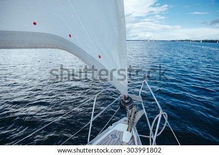 View from the board of a sailing yacht on the waters, sailing ships and the forest growing along the coast, as well as people's homes.