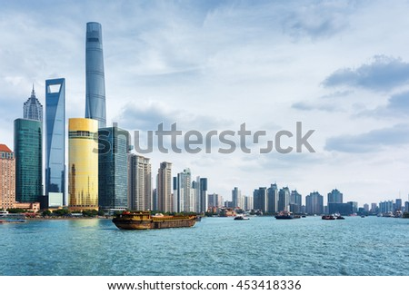 View from the Bund in Shanghai, China. The Shanghai Tower, the Shanghai World Financial Center and other skyscrapers of downtown are visible at left. Self-propelled barges on the Huangpu River. - stock photo