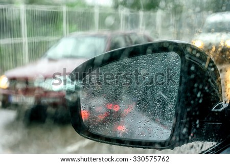 View from the car glass in to the car mirror on the rainy day - stock photo