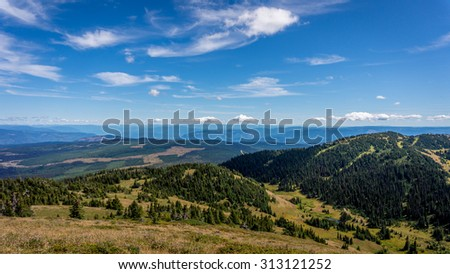 View from the 7000 ft summit of Tod Mountain of the Sushwap highlands in central British Columbia on a beautiful summer day under blue skies with a few clouds - stock photo