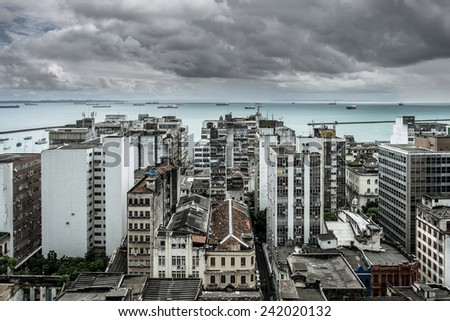 View from the Old Town of Salvador de Bahia/Brazil at the abandoned lower Town. Ships lying in the Bay waiting. A Sky with stormy clouds. - stock photo