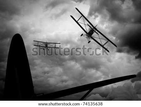 View from the open rear cockpit of enemy plane over the tail and rear wing. Two double wing biplane giving chase through storm and smoke filled clouds. Original Illustration - stock photo