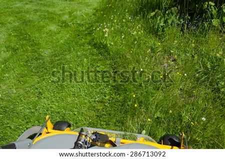 View from the seat on a riding mower when cutting the lawn - stock photo