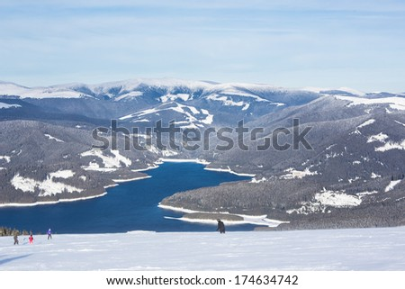 View from the top of a ski slope towards a lake