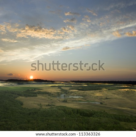 View from the top of the mountain. Colorful sunset. Blue sky and white clouds. Green field and summer forest. Beauty landscape - stock photo