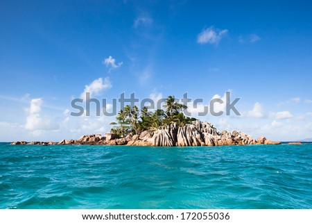 View from the turquoise sea to the exotic island of St. Saint  Pierre with granite rocks and coconut palm trees, Seychelles Africa