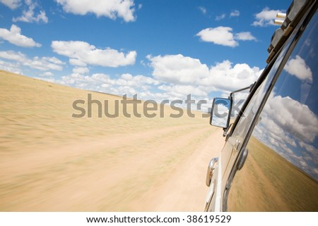 view from the window of an SUV on the desert - stock photo