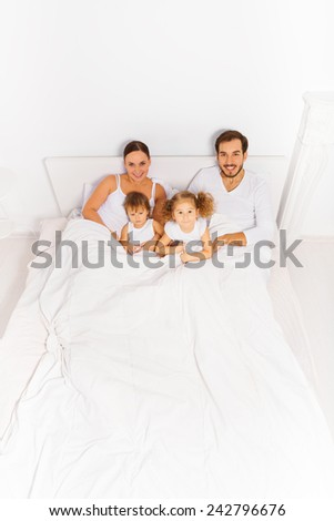 View from top of parents and two kids on white bed - stock photo