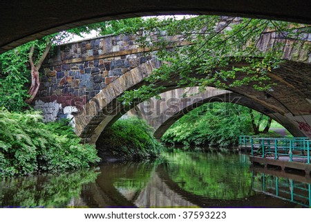 View from underneath a roadway with a pathway along the river. - stock photo