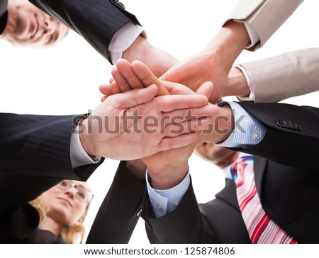 View from underneath of a group of businesspeople standing in a circle placing their hands on top of each other - stock photo