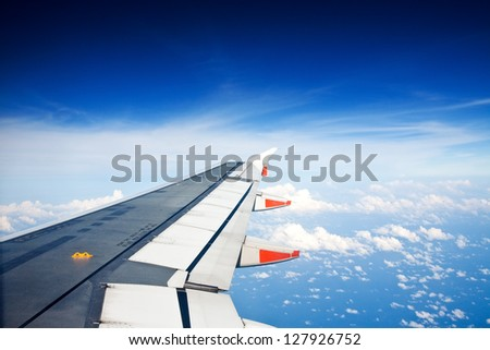 View from window seat of an airplane overlooking blue sky and clouds. - stock photo