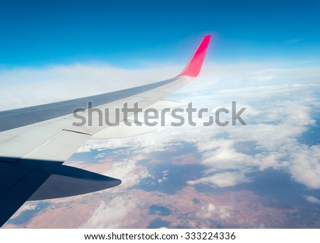 View from window seat of an airplane, wing, blue sky and clouds. - stock photo