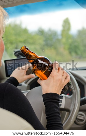 View inside a car from the back passenger seat of a woman driving holding a bottle of bear in one hand while steering - stock photo