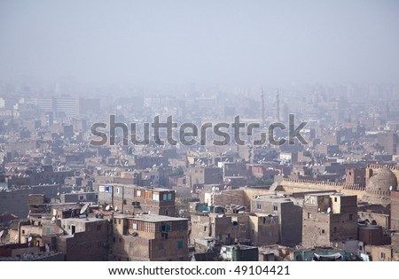 View into a misty city of Cairo in Egypt over roof top slums and mosques - stock photo