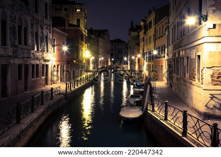 view into a small canal in Venice at night - stock photo