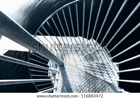 View looking down a metal spiral staircase turning around a central pole as it winds its way downwards - stock photo