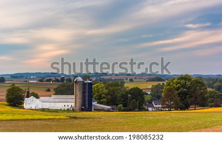 View of a barn and silos on a farm in rural Lancaster County, Pennsylvania. - stock photo