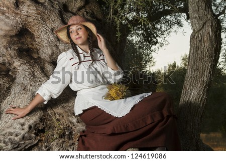 View of a beautiful girl in a classic dress in a countryside set in the shade of a very old olive tree.