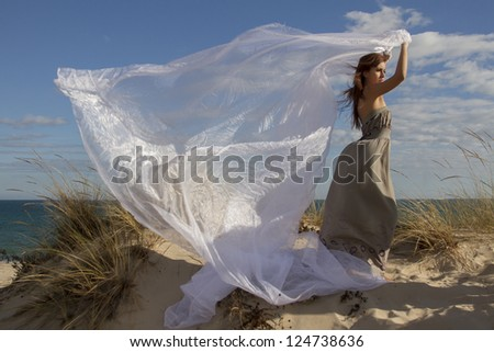 View of a beautiful girl in beach holding a beautiful long white cloth in the wind.