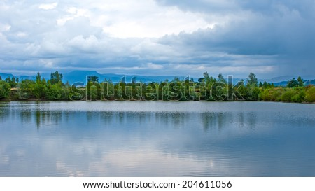 View of a beautiful lake and mountains before the storm, dark clouds are gathering - stock photo