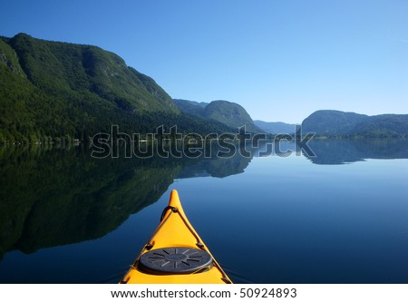 View of a beautiful mountain lake with sea kayak in the foreground - stock photo