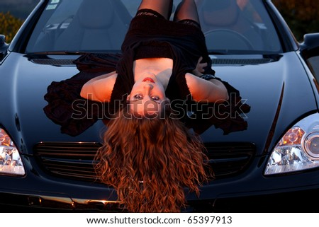 view of a beautiful woman on top of a sports car. - stock photo