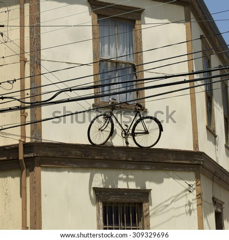 View of a bicycle on the ledge of a house, Valparaiso, Chile - stock photo