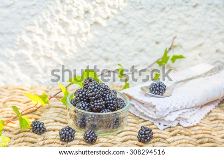View of a bowl of blackberries on wicker background. Background with space for text. - stock photo