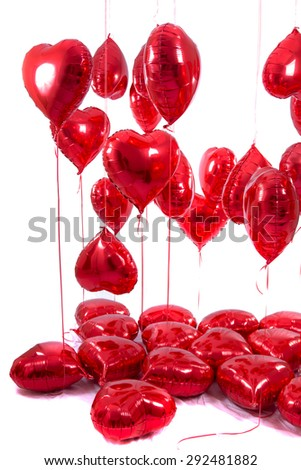View of a bunch of red heart balloons isolated on a white background.